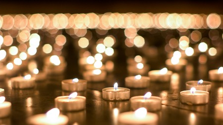 believers: Large group of burning candles placed on the ground by believers