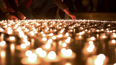 blessings: Few people saying their blessings and placing the candles on the ground Stock Photo