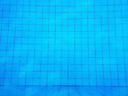 above water: The bottom of a pool view from above through the water.