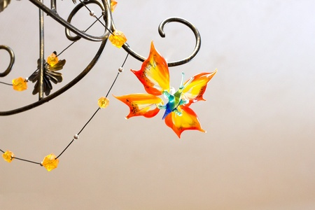 chandelier  with daecorative glass butterfly on light background photo