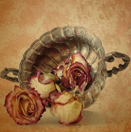 grunge old roses in silver vase on vintage paper background photo