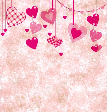 different pink hanging hearts on the grunge light paper background photo