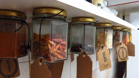 Potten met kruiden en specerijen opknoping van plank in keuken Stockfoto
