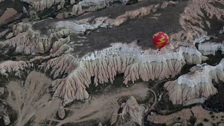 Hot Air Balloon Flying Over Landscape in Cappadocia