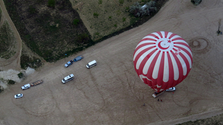 Turkish Red and White Hot Air Balloon Landing As Seen From Above in the Sky