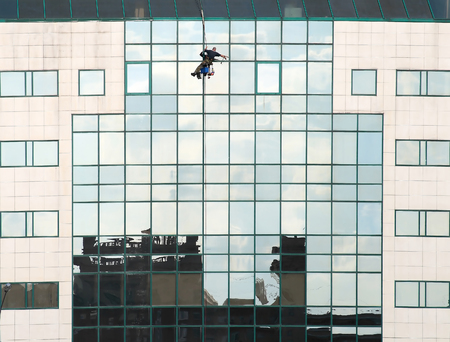 working construction worker on the specular facade of the enormous, contemporary building 版權商用圖片