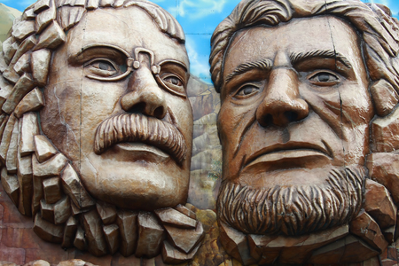 Enormous faces of people on the facade of attraction in the park photo