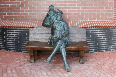 ethnographical: Statue of man of that sitting on the bench. Ethnographical complex fish village