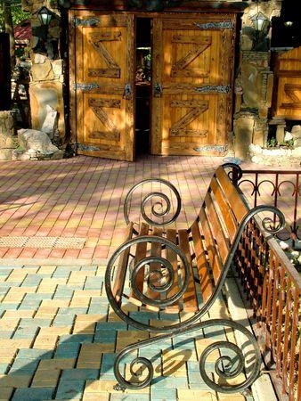 カフェの入り口前に庭のベンチ 写真素材