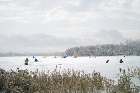 Fishermen on ice of the frozen lake photo