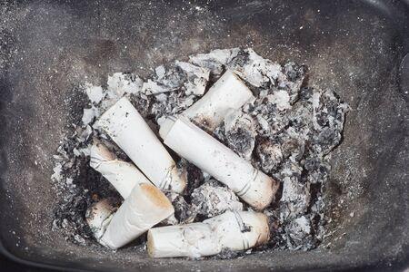 Black ash-tray with cigarette cigarette-ends photo