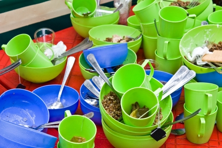 kitchen scraps: Large mountain of dirty dishes on the kitchen of camp of tourists