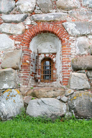 Small window monastic cell behind bars in a thick stone wall photo