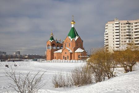 Moscow, municipal landscape. Church ashore the frozen lake photo