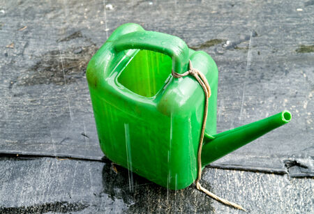 wateringcan: Drops of pouring rain on a green garden watering-can