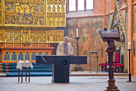 inwardly: GERMANY, FRANKFURT AM MAIN - May 07.2014: Imperial cathedral of saint Bartholomew. A pastor reads prayer on a background an ancient iconostasis