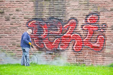 municipal: GERMANY, FRANKFURT AM MAIN - May 07.2014 : Worker of municipal service of city cleans a wall from graffiti