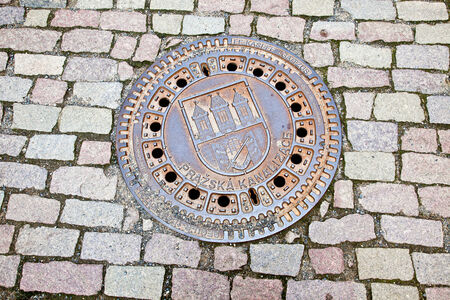 observational: Cover with the coat of arms on to Prague sewer manhole