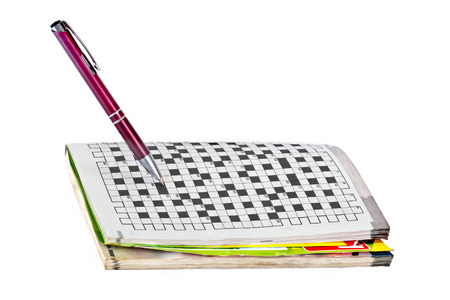 Ballpoint pen and a collection of crossword puzzles isolated on white background photo