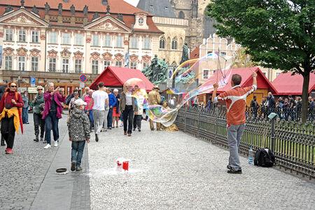 young fellow: CZECH REPUBLIC, PRAGUE - April 28.2014: A young fellow inflates enormous soap bubbles for entertainment of public