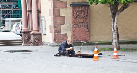 GERMANY, FRANKFURT AM MAIN - May 07.2014: Worker sits on the edge of the manhole