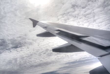 manoeuvre: Wing of the plane on a background of sky and sun