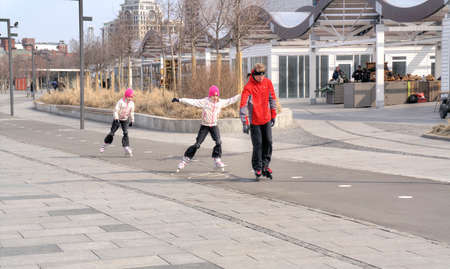 going places: MOSCOW, RUSSIA - March 28.2015: Father and daughter ride on roller skates in the Crimean waterfront