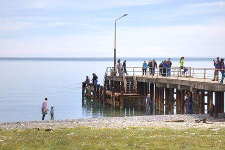 climatic: PITSUNDA, ABKHAZIA - April 26.2015: Black Sea coast of climatic resort Pitsunda. Fishermen and tourists on a pier