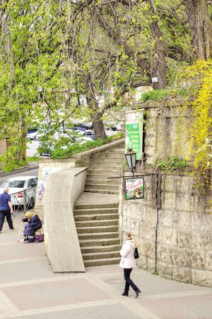 wretched: KISLOVODSK, RUSSIA - April 30.2015: City landscape. Stairs in a prestigious restaurant and a beggar on the sidewalk