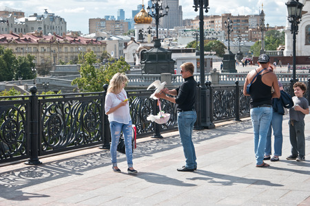 persuades: MOSCOW, RUSSIA - July 22.2015: Man-photographer offers to the girl to be photographed with hand pigeons