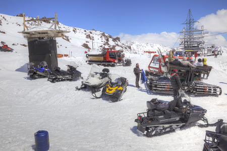sightseers: CAUCASUS, RUSSIA - May 01.2015: Snow grooming and snowmobiles next to the station of ropeway on the slope of mountain Elbrus