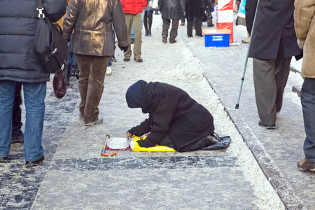 begs: MOSCOW, RUSSIA - January 01.2010: Elderly woman begs alms on a snow-bound street in the center of city