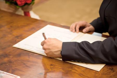 registry: Marriage. Bridegroom puts his signature to the document