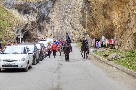 narrowly: CHEGEM CANYON, CAUCASUS, RUSSIA - May 02.2015: Cars and riders on horseback on the road in the Chegem gorge