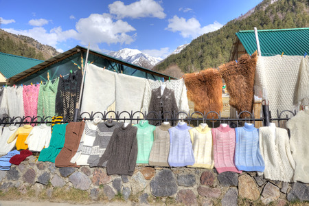 warm things: VALLEY NARZAN, CAUCASUS, RUSSIA - May 01.2015: Souvenirs and warm things on the counter of little market in Valley of Narzan Stock Photo