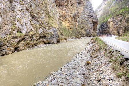 narrowly: Road to the Chegem gorge along the river Chegem Stock Photo