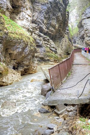 narrowly: CHEGEM CANYON, CAUCASUS, RUSSIA - May 02.2015: Road to the Chegem gorge along the river Chegem. Dilapidated water verge of the road