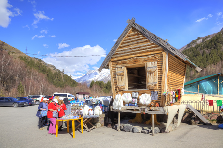 warm things: VALLEY NARZAN, CAUCASUS, RUSSIA - May 01.2015: Fairytale log cabin and little market of the warm knitted things