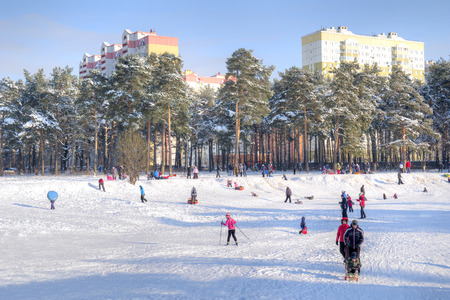 children pond: MOSCOW, RUSSIA - January 24.2016: Children and adults go for a drive from the steep bank of the frozen pond