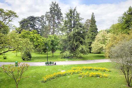Little park with flowerbeds and trees in the center of city Geneva by an early spring