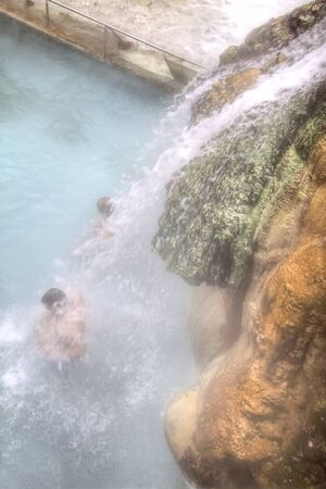 radon: People in the pool standing under a waterfall jets with healing thermal spring water