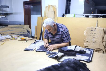 inwardly: GREECE, KASTORIA - March 12.2016: Workshop on sewing female fur coats on a factory