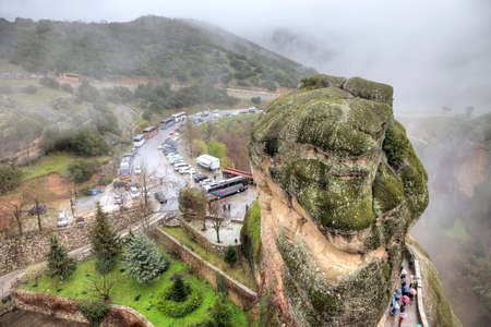 busses: METEORA, GREECE - March 13.2016: Tourist busses on a stand before a monasterial complex near a mountain.