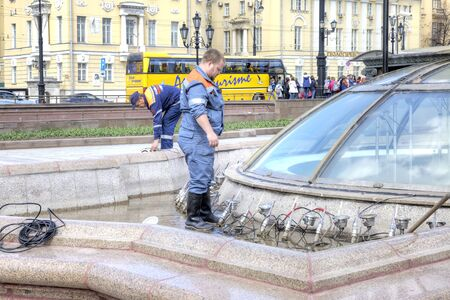 prophylaxis: MOSCOW, RUSSIA - April 24.2016: Worker of municipal service of city does the prophylaxis of sprayers of fountain