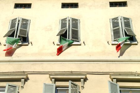 reggio emilia: State flags of Italy on the windows of facade of house in city Reggio Emilia