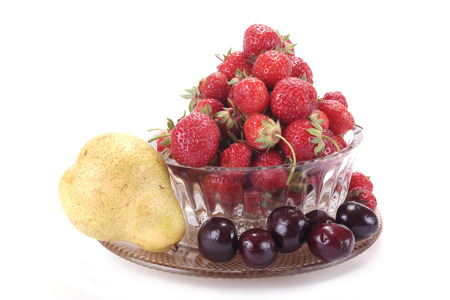 gean: Berries of strawberry and merry in a glass vase on a white background