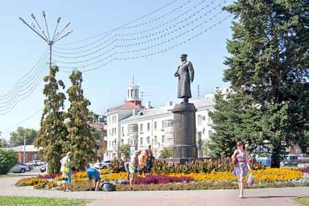 passerby: BELGOROD, RUSSIA - August 30.2016: Brigade of workers engage in planting trees and shrubs of municipal service work on a flowerbed next to a monument to general Apanasenko