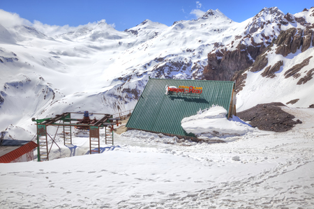 CAUCASUS, RUSSIA - May 01.2015: Covered by snow on the roof alpine hotel on the hillside of mountain Elbrus