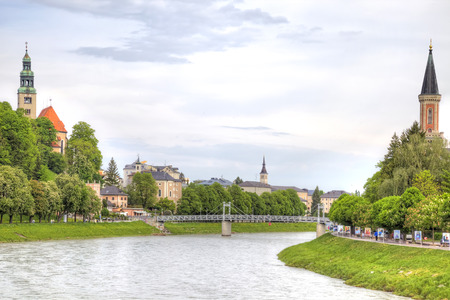 navigable: SALZBURG, AUSTRIA - May 05.2012: City landscape. Salz River and the spiers of the Catholic Church on its banks