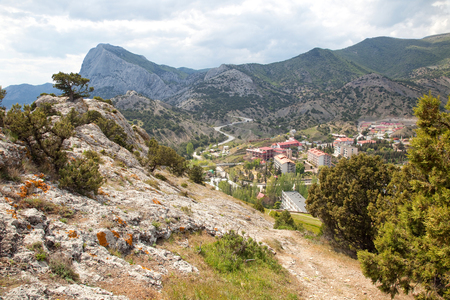 sudak: View of a mountain road and the town of Sudak with the top of the mountain Stock Photo